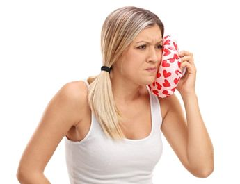 woman applying cold compress to face