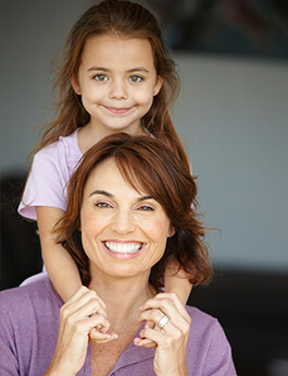 Mother and young daughter with red hair smiling