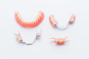 Collection of full and partial dentures on white background