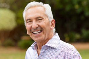 Older man with dental implants smiling